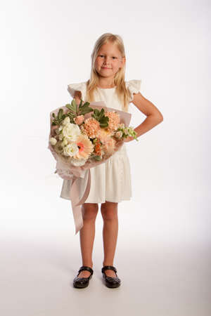 Studio portrait of cute blonde girl in white dress with beautiful gift bouquet, white background, selective focus
