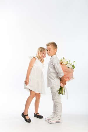 Studio portrait boy gives girl festive bouquet, congratulatory concept, white background, copy space