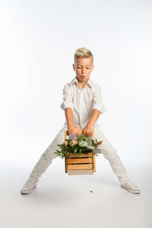 Studio portrait of fashionable blond caucasian boy with wooden basket of flowers, white background, copy space