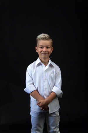 Studio portrait of stylish caucasian blond boy in shirt and tie, black background, copy space Reklamní fotografie