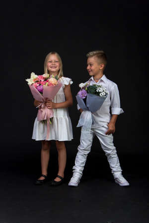 Studio portrait girl and boy with bouquets, congratulatory concept, black background, copy space Reklamní fotografie