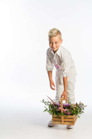 Studio portrait of fashionable blond caucasian boy with wooden basket of flowers, white backdrop, copy space