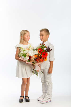 Studio portrait boy gives girl festive bouquet, congratulatory concept, white backdrop, copy space Reklamní fotografie