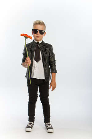 Studio portrait of fashionable blond caucasian boy with single gerbera flower, white backdrop, copy space Reklamní fotografie