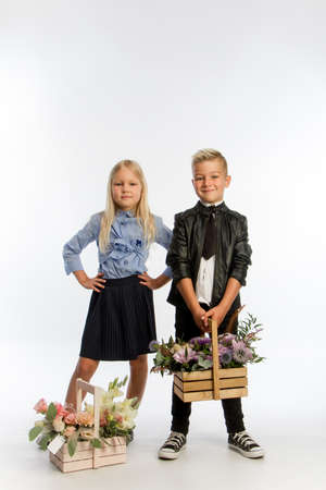 Studio portrait boy and girl dressed school uniform with greeting flower arrangements in wooden baskets, congratulatory concept, white backdrop, copy space