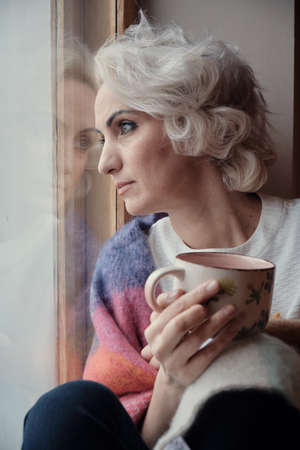 Unhappy pensive mature woman drinking tea and looking out window, lockdown and isolation concept, selective focus