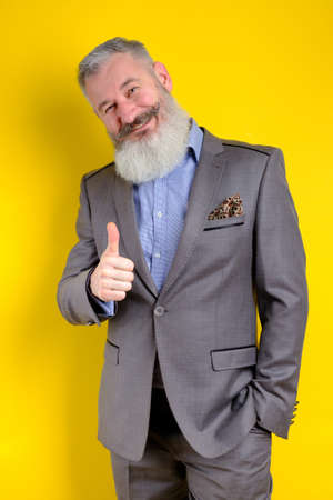 Studio portrait mature businessman dressed in gray suit shows thumb up, successful business concept, yellow background 版權商用圖片
