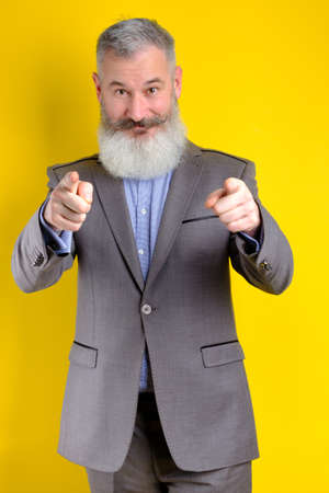Studio portrait mature businessman dressed in gray suit points to camera, I choose you concept, yellow background 版權商用圖片