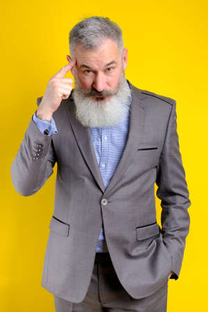 Studio portrait mature businessman dressed in gray suit pointing to head with forefinger, great idea or thought concept, good memory, yellow backdrop.