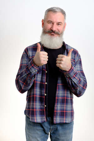 Studio portrait mature bearded man dressed in casual clothes shows thumbs up, successful concept, white background Banco de Imagens