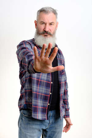 Studio portrait of mature bearded man in casual clothes shows hand stop sign, gesture no more, white background, copy space