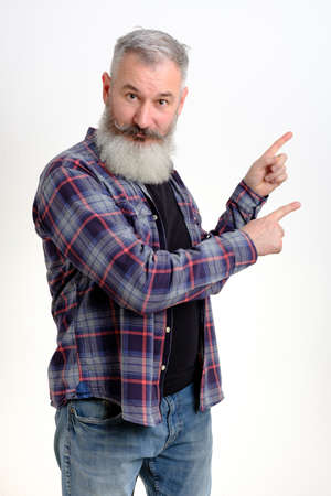 Studio portrait mature man dressed in casual clothes points aside, I choose this, white background