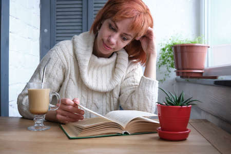 Young adult red haired girl relaxing at home with mug of hot beverage and book in domestic kitchen, relaxing during quarantine Banco de Imagens