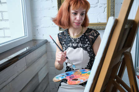 Portrait of concentrated beautiful young adult red head woman painter holding art palette and painting on canvas with brush at home Banco de Imagens