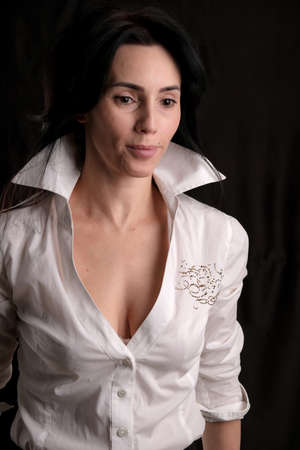 Portrait of beautiful mature brunette woman dressed in white shirt isolated on black backdrop, copy space Banco de Imagens