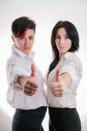 Portrait of two laughing women in white clothes standing face to face with thumbs up isolated over white backdrop Banco de Imagens