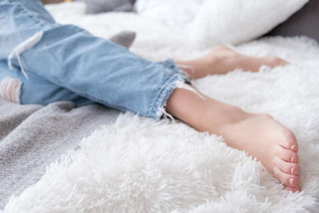 Close up of barefoot attractive female legs dressed blue jeans in bed, home relaxation and rest Banco de Imagens