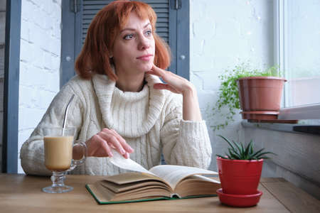 Young adult red haired girl relaxing at home with mug of hot beverage and book in domestic kitchen Banco de Imagens