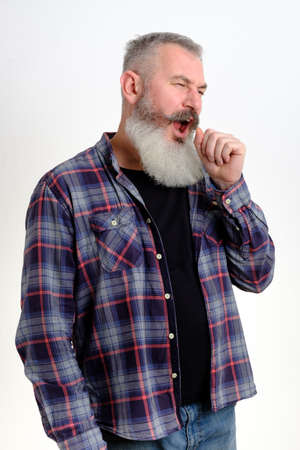 Portrait of sleepy mature bearded man in casual clothes yawning and covering mouth with hand, feeling exhausted, lack of sleep. I need rest concept on white background