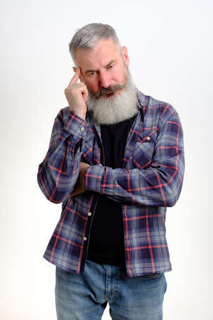 Studio portrait of pensive mature bearded man dressed in jeans and plaid shirt, looking worried, thinking about problems, white background Banco de Imagens