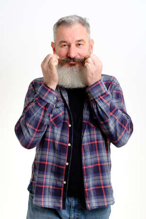 Studio portrait of mature bearded man in casual clothes twirling his mustache and looking at camera over white backdrop