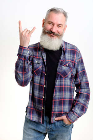 Portrait of mature bearded man in casual clothes showing horns up gesture