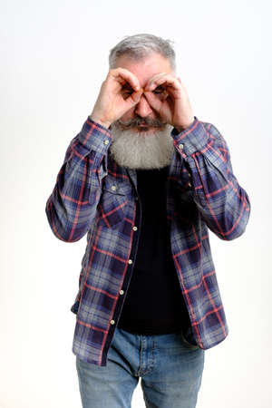 Studio portrait of mature bearded man who made binoculars with palms, searching concept, white background