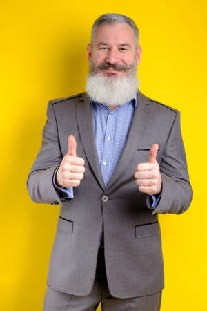 Studio portrait mature bearded businessman dressed in gray suit shows thumbs up, successful business concept, yellow background
