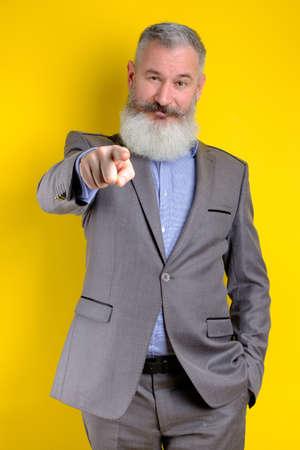 Studio portrait mature businessman dressed in gray suit points on camera, I choose you concept, yellow background Banco de Imagens