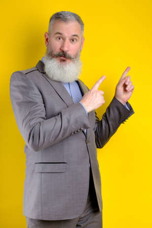 Studio portrait mature businessman dressed in gray suit points aside, I choose you this, yellow backdrop