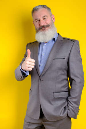 Studio portrait mature bearded businessman dressed in gray suit shows thumb up, successful business concept, yellow background
