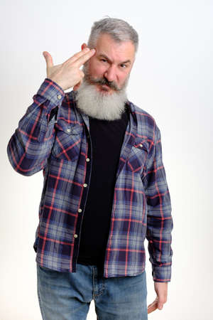 Studio portrait of mature bearded man pointing finger gun gesture to head. Suicide gesture. Isolated on white background.