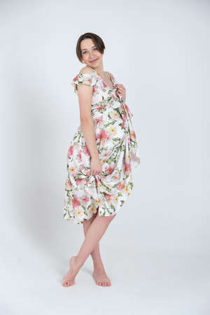 Studio portrait of cheerful young pregnant woman in summer dress on white grey background, happy pregnancy concept Banco de Imagens