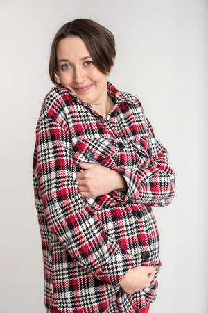 Studio portrait of young adult woman in warm home clothes, happy pregnancy concept, white backdrop Banco de Imagens