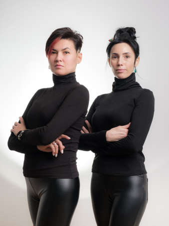Portrait of two confident women dressed in black clothes standing side by side isolated over white background