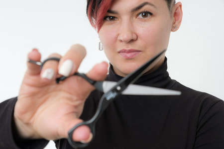 Halflength portrait of young adult barber woman on white background holding metal professional hairdressing scissors, modern barber girl concept