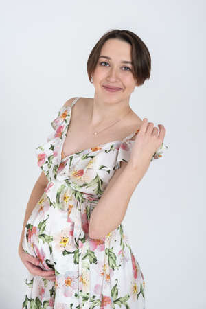 Studio portrait of cheerful young pregnant woman in summer dress on white grey background, happy pregnancy concept 版權商用圖片
