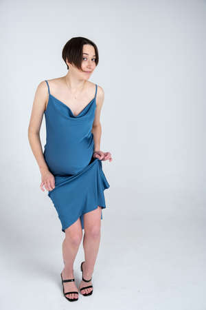 Studio portrait of young adult pregnant woman in blue dress dancing on white grey background, happy pregnancy concept