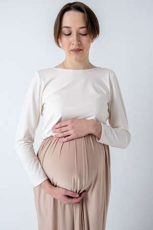 Studio portrait of elegant young adult pregnant woman in white beige dress on white backdrop, happy pregnancy concept