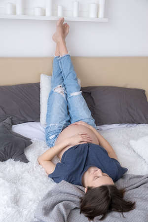 Pregnant young adult woman dressed jeans and t-shirt lying on bed relaxing with legs raised up