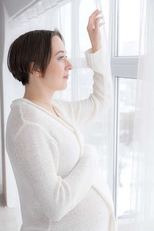 Young adult pregnant woman in white negligee standing at the window, selective focus