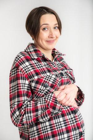 Studio portrait of young adult woman in warm home clothes, happy pregnancy concept, white backdrop Archivio Fotografico