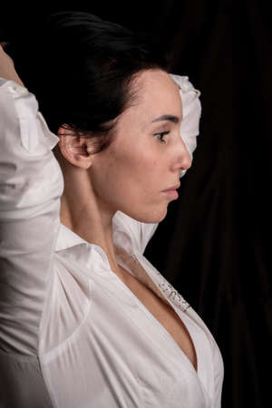 Portrait of beautiful mature brunette woman dressed in white shirt isolated on black backdrop, copy space 版權商用圖片