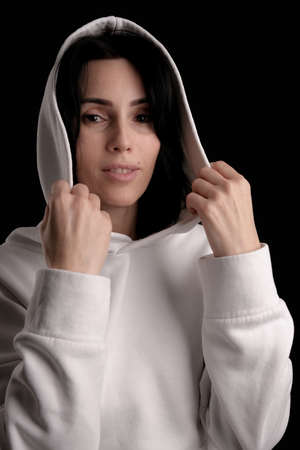 Portrait of beautiful mature brunette woman dressed in white hoodie isolated on black backdrop, copy space