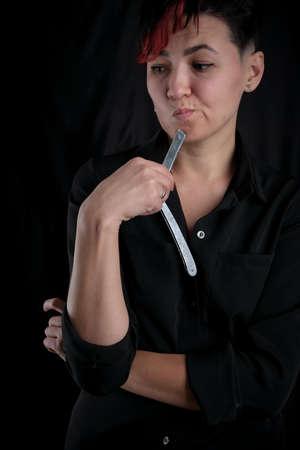 Half length portrait of young adult barber woman on black background holding vintage straight razor, modern barber girl concept