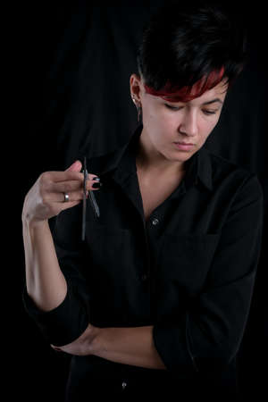 Half length portrait of young adult barber woman on black background holding vintage straight razor, modern barber girl concept