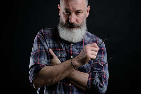 Studio portrait of mature bearded man in casual clothes with eyeglasses in hand looking directly at camera, informal lifestyle, black background.