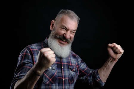 Portrait of happy joyful and emotive bearded mature european guy, raising fists high and yelling, triumphing or cheering while watching football match, black background