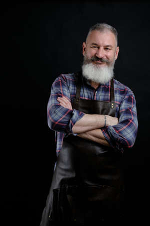 Portrait of handsome mature bearded man dressed leather apron isolated on black backdrop, caucasian workman with beard smiling 版權商用圖片
