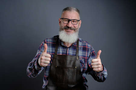 Portrait of handsome mature bearded man dressed leather apron gesturing thumbs up over gray background, caucasian worker with beard smiling